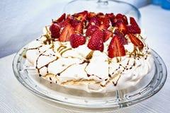 Torta sabrosa y hermosa del merengue adornada con el corte rojo de las fresas por la mitad y adornada con caramelo líquido Imágenes de archivo libres de regalías