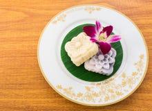 Torta tallada amarilla y negra de Mochi en la hoja tailandesa del plátano en una pizca imagen de archivo