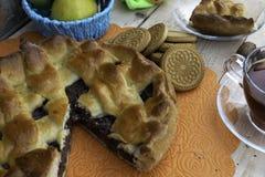 Torta, uma fatia de torta de maçã com cereja e nozes, um copo do chá, maçãs em uma cesta, nozes e cookies na tabela imagens de stock royalty free