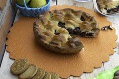 Torta, uma fatia de torta de maçã com cereja e nozes, um copo do chá, maçãs em uma cesta, nozes e cookies na tabela fotos de stock royalty free