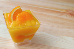 Torta vibrante de la mandarina del color rematada con la naranja fresca en bol de vidrio Foto de archivo