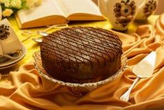 Torta y espátula festivas de chocolate para la empanada, utensilios del té en mantel imágenes de archivo libres de regalías
