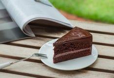 Torta y libro de chocolate en la tabla de madera Imágenes de archivo libres de regalías