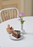 Torta y postre deliciosos de chocolate cerca con las flores en la tabla blanca en café Fotografía de archivo libre de regalías