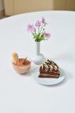 Torta y postre deliciosos de chocolate cerca con las flores en la tabla blanca en café Imagen de archivo libre de regalías