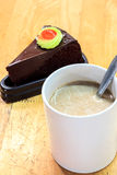 Torta y taza del café, cuchara en fondo de madera de la falta de definición Foto de archivo