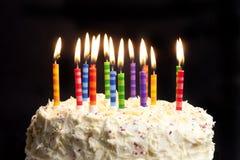 Torta y velas de cumpleaños en fondo negro Foto de archivo