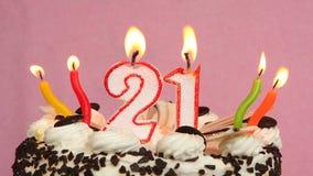 Torta y velas felices de cumpleaños 21 en un fondo rosado metrajes