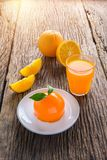 Torta y vidrio anaranjados de zumo de naranja fresco en etiqueta de madera del grunge Foto de archivo libre de regalías