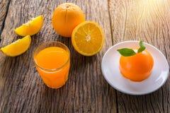 Torta y vidrio anaranjados de zumo de naranja fresco en etiqueta de madera del grunge Imagenes de archivo