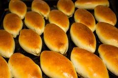 Tortas calientes rusas en el horno en una plataforma Empanadas de oro en un primer negro del fondo fotos de archivo