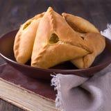 Tortas caseiros com batatas e cebolas em uma bacia cerâmica no livro de receitas velho Imagem de Stock
