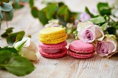 Tortas coloridas de los macarrones y flores frescas Fotografía de archivo