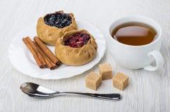 Tortas com airelas, mirtilos, canela, açúcar, chá no copo, Foto de Stock Royalty Free