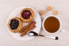Tortas com airelas, mirtilos, canela na placa, açúcar, chá Imagem de Stock Royalty Free