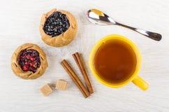 Tortas com mirtilos, airelas, açúcar, canela, chá, colher o Fotografia de Stock Royalty Free