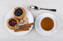 Tortas com mirtilos, airelas, açúcar, canela, chá no copo, Foto de Stock