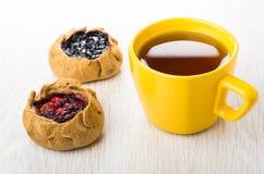 Tortas com mirtilos, airelas, chá no copo amarelo na tabela Fotografia de Stock Royalty Free
