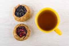 Tortas com mirtilos, airelas e chá no copo amarelo Fotografia de Stock Royalty Free