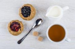 Tortas com mirtilos, airelas, leite, chá, açúcar e colher Fotografia de Stock Royalty Free