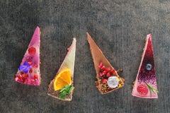 Tortas crudas del vegano con la fruta y las semillas, adornadas con la flor, fotografía del producto para la pastelería Foto de archivo