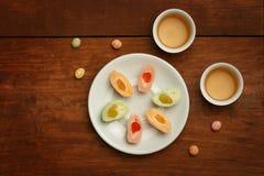 Tortas de arroz coloridas del mochi en la placa blanca, tazas de la porcelana con GR Fotografía de archivo libre de regalías