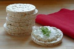 Tortas de arroz, una con el queso cremoso e hierbas en la madera, servilleta roja Imágenes de archivo libres de regalías