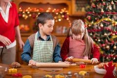 Tortas de la Navidad de la hornada de la abuela y de la niña y del muchacho en th Fotografía de archivo libre de regalías