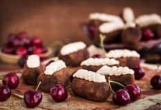 Tortas de las bolas del ron del chocolate adornadas con la cereza poner crema y fresca Imagen de archivo libre de regalías