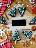Tortas de miel adornadas como árboles de navidad y un smartphone con una pantalla vacía en el centro Imagen de archivo