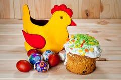 Tortas de Pascua y huevos pintados con el pollo de Pascua en una tabla de madera Fotos de archivo