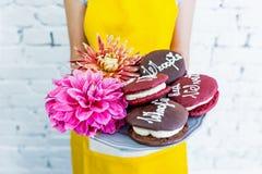 Tortas de Whoopie em uma bandeja com flores, mãos do ` s das mulheres Felicitações Fotografia de Stock
