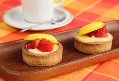 Tortas e chávena de café da morango na tabela alaranjada Imagem de Stock Royalty Free