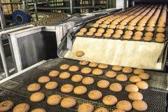Tortas en la banda transportadora o la línea automática, proceso de la hornada en fábrica de la confitería Industria alimentaria, imagen de archivo libre de regalías