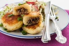 Tortas fritadas da batata com cogumelos e salada em uma placa foto de stock royalty free