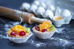 tortas, huevos en una bandeja con un rodillo y un batidor en la tabla con la harina fotos de archivo