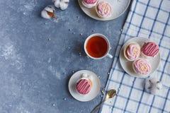Tortas poner crema en una placa, una taza de té en una tabla de mármol gris Desayuno fotografía de archivo