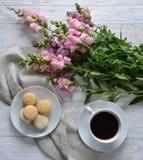 Tortas, una taza de café y flores en la tabla Foto de archivo libre de regalías