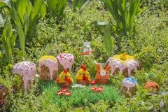 Tortas y huevos de Pascua en sombreros hechos punto divertidos en el jardín Imagen de archivo