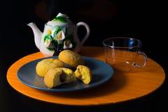 Tortas y taza de té en el fondo negro Fotografía de archivo libre de regalías