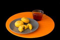 Tortas y taza de té en el fondo negro Fotos de archivo libres de regalías
