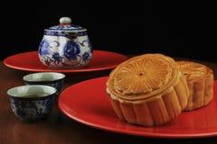 Torte di luna e POT del tè in piatto rosso Fotografia Stock