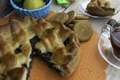 Torte, eine Scheibe des Apfelkuchens mit Kirsche und Walnüssen, eine Tasse Tee, Äpfel in einem Korb, Walnüsse und Plätzchen auf d lizenzfreie stockbilder