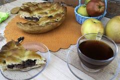 Torte, eine Scheibe des Apfelkuchens mit Kirsche und Walnüssen, eine Tasse Tee, Äpfel in einem Korb, Walnüsse und Plätzchen auf d lizenzfreie stockfotos