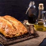 Torte eingefettet mit Olivenöl auf einem braunen Hintergrund Lizenzfreies Stockfoto
