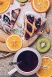 Torte mit Stau von den Beeren mit einer Tasse Tee, getrocknete Orangen, Kiwischeiben und Nüsse Köstliche Torte auf einem Holztisc Lizenzfreies Stockfoto