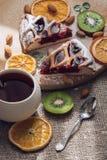 Torte mit Stau von den Beeren mit einer Tasse Tee, getrocknete Orangen, Kiwischeiben und Nüsse Köstliche Torte auf einem Holztisc Lizenzfreies Stockbild