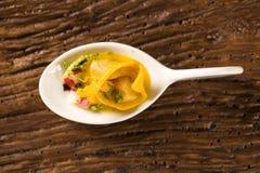 Tortelline del camarón, salsa de la mañana, rábano y sal negra en una cuchara Foto de archivo