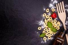 Tortellini και αλεύρι σε ένα μαύρο πιάτο πετρών Στοκ φωτογραφίες με δικαίωμα ελεύθερης χρήσης