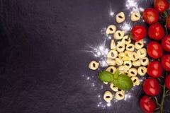 Tortellini και αλεύρι σε ένα μαύρο πιάτο πετρών Στοκ Εικόνα